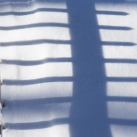Shadows | Nearly covered by the snow, a pickett fence casts a long shadow in the afternoon light. (Herald / Tim Calabro)